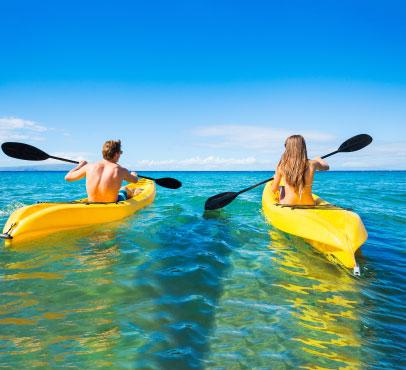 Couple enjoying a kayaking adventure on their Bahama Paradise Cruise